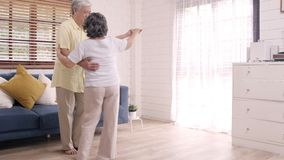 Asian elderly couple dancing together while listen to music in living room at home.