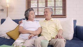 Asian elderly couple feeling happy smiling and looking to camera while relax on the sofa in living room at home. stock video