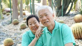 Happy Asian elderly couple laugh together in green natural park Royalty Free Stock Images