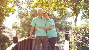 Happy Asian elderly couple laugh together in green natural park Royalty Free Stock Photo