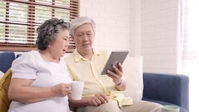 Asian elderly couple using tablet and drinking coffee in living room at home.