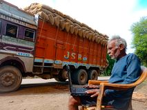 asian elderly man learning about laptop computer system at road side in india January 2020