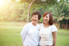 Asian elderly mother and grown daughter. Portrait of happy Asian elderly mother and daughter, senior adult women and grown child. Outdoors family at nature park stock photos