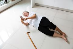 Asian elderly people with walking stick and using the phone to call for help,sick senior woman with headache,backache lying on the stock photos