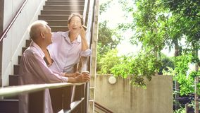 Asian elderly professional couple talking outdoor morning in cit. Asian elderly professional couple talking outdoor morning in modern building stock photography