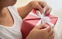 Asian elderly woman holding on white ribbon of red gift box. Close up on hands. Asian elderly woman holding on white ribbon of red gift box. Birthday, Christmas Royalty Free Stock Photography