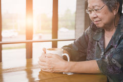 Asian elderly woman sitting and resting in cafe coffee shop with. Asian elderly woman sitting and resting in coffee shop with cup of cappuccino coffee. Elder Stock Photos