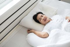 Asian elderly woman snoring because due to tired of work,Female snor while sleeping on bed royalty free stock photos