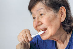 Asian elderly woman with a toothbrush. royalty free stock photography
