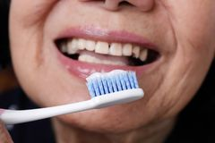 Asian elderly woman trying use toothbrush ,hand tremor. Dental health stock photo