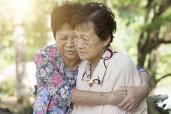 Asian elderly women hugging. Candid shot of Asian elderly women consoling her friend at outdoor park in the morning royalty free stock images
