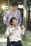 Asian elderly women playing swing at outdoor playground Stock Photos