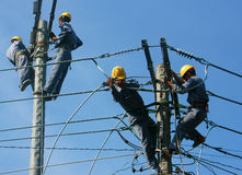 Asian electrician climb high, work on electric pole royalty free stock photos