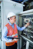 Asian Electrician at panel on construction site Stock Photo