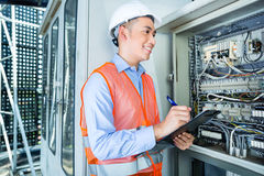 Asian Electrician at panel on construction site. Asian Indonesian Technician or electrician making function test on breaker box or switchbox with power lines on Stock Photography