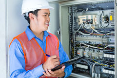 Asian Electrician at panel on construction site. Asian Indonesian Technician or electrician making function test on breaker box or switchbox with power lines on Royalty Free Stock Photos