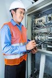 Asian Electrician at panel on construction site Stock Image