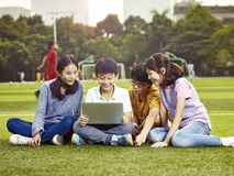 Asian elementary school children using laptop outdoors. Four asian elementary school boys and girls sitting on playground using laptop computer together Stock Photo