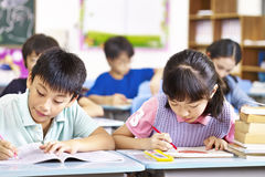 Asian elementary school students in classroom. Asian primary school students studying in classroom Stock Image