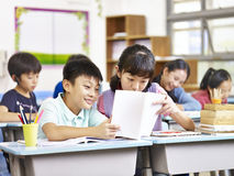 Asian elementary school students in classroom. Asian elementary schoolgirl and schoolboy sharing a book in classroom Stock Photos