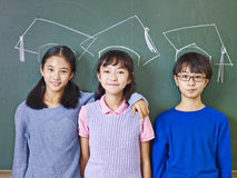 Asian elementary school students standing underneath chalk-drawn doctoral hats. Three asian elementary school children standing in front of chalkboard underneath stock photo