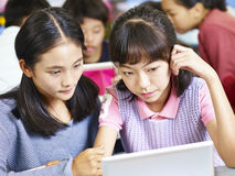 Asian elementary school students working in groups. Two asian elementary school girls looking at tablet computer thinking hard while working in groups Stock Photography
