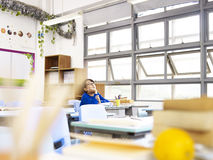 Asian elementary schoolboy sitting alone in classroom. Asian pupil sitting alone in classroom looking up at the ceilings Royalty Free Stock Photos