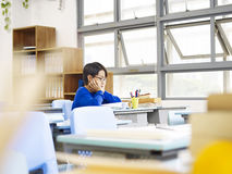 Asian elementary schoolboy sitting alone in classroom. Unhappy asian elementary school pupil sitting alone in classroom Stock Photo