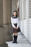 Asian elementary schoolgirl. 9-year old asian elementary schoolgirl standing in hallway in school uniform Royalty Free Stock Images