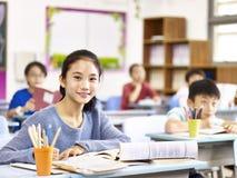 Asian elementary schoolgirl in class Stock Photo