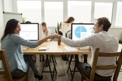Asian employee fist bumping caucasian colleague sitting in multi. Asian employee fist bumping caucasian colleague sitting together in multiracial coworking Royalty Free Stock Image