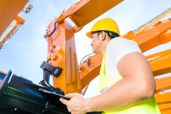 Asian engineer controlling shovel excavator Stock Photo