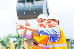 Asian engineer discussing plans on construction site Stock Photography