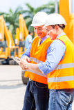 Asian engineer discussing plans on construction site Stock Photos