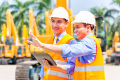 Asian engineer discussing plans on construction site Royalty Free Stock Photography