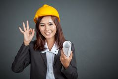 Asian engineer girl hold a blueprint show Ok sign Royalty Free Stock Photos