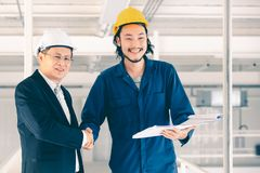 Asian engineer handshakes with executive engineer stock photography