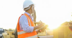 Asian engineer with hardhat using tablet pc computer inspecting. And working at construction site stock photography