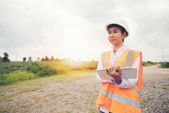 Asian engineer with hardhat using tablet pc computer inspecting. And working at wind turbine farm Power Generator Station stock image