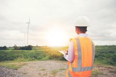 Asian engineer with hardhat using tablet pc computer inspecting. And working at wind turbine farm Power Generator Station royalty free stock photography