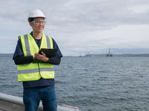 An asian engineer holding a clip board and standing Stock Image