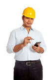 Asian engineer man hold a cellphone and a pen Royalty Free Stock Images