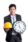 Asian engineer man hold hardhat and a clock Royalty Free Stock Photography