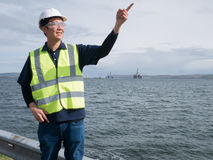 An asian engineer pointing and standing in front of semi submers Royalty Free Stock Images