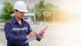 Asian engineer in safety uniform and white helmet taking note on clipboard on blurred industry plant background. With sun light effect for industrial concept Stock Image
