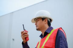 Asian engineer in safety uniform and white helmet using walkie-talkie on blurred industry plant background Stock Image