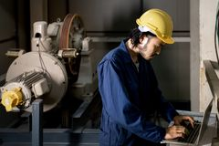 Asian engineer using notebook in factory stock photography