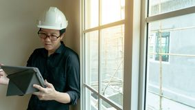 Asian engineer using tablet on construction site. Young Asian engineer with helmet and eyeglasses using digital tablet near the window at construction site stock photos