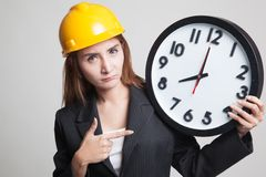 Asian engineer woman in bad mood with a clock. Royalty Free Stock Photography
