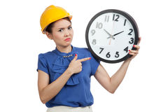 Asian engineer woman in bad mood with a clock Stock Image